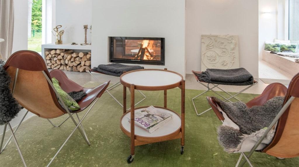 I husets andra vardagsrum finns inbyggd braskamin, och panoramafönster med platsbyggd soffa framför, vilket ger känslan av att sitta mitt ute i naturen.