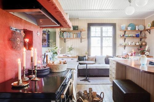 Väggen bakom den gamla vedspisen har putsats i en varmröd kulör. Här finns nu även en ny ugn. Ljushållare från loppis. Brödkorg från Stenmöllans Antik i Skåne. Allt glas har Annette gjort.