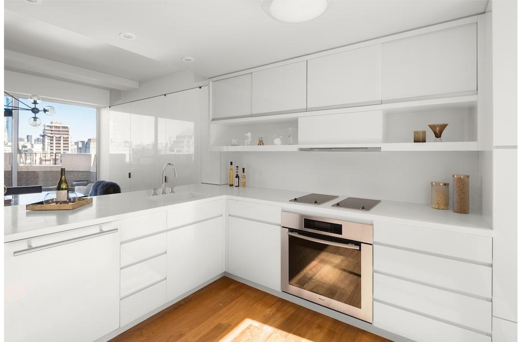 Köket med vita skåpluckor.
