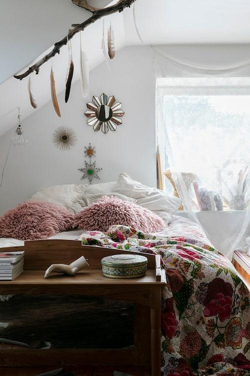 Parets sovrum ligger på andra våningen och är mysigt inrett med rosa kuddar, blommigt överkast och dekorativa detaljer. Överkast och stjärnspegel, Indiska. Rosa kuddar, H & M Home.