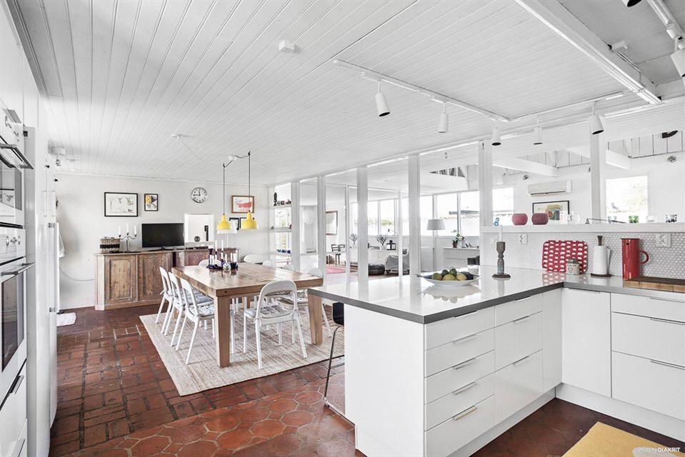 Köket i vitt på markplan har stor matplats, gammaldags skafferi och egen utgång till uteplats.