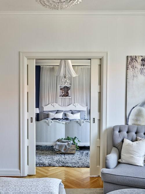 Linnea och Carstens vackra sovrum ligger innanför vardagsrummet och förbinds med gedigna skjutdörrar.