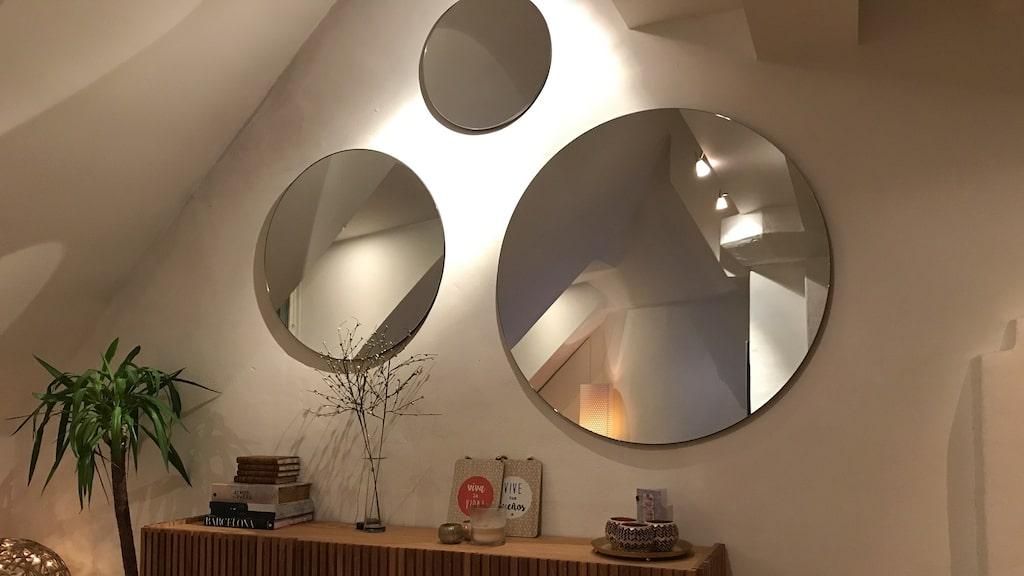 Ett nyköpt sidobord i vardagsrummet är både snyggt och praktiskt. De runda speglarna skapar ett ljusspel från takfönstret.