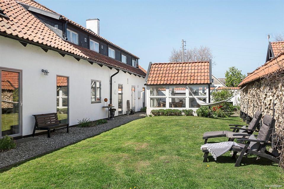 Huset, glashus samt vedförvaring.