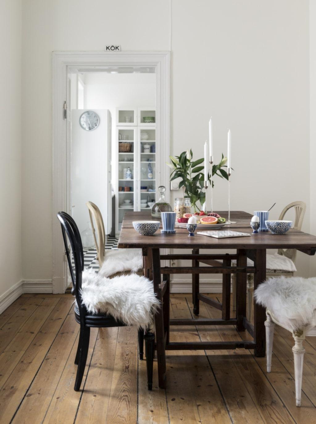 Rustikt bord. Runt det ärvda slagbordet från 1700-talet samsas loppisfyndade stolar i bondrokoko-stil. På bordet står silverljusstakar, design Richard Hutten för Skultuna. Muggar Margareta från Göteborgsfabrikerna.
