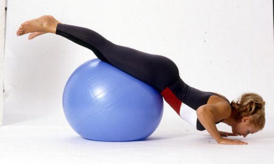 2 A. PUSH-UPS: Lägg dig framstupa på bollen så att höfterna får stöd. Placera händerna plant mot golvet på axelbrett avstånd med sträckta armar. Håll ihop benen och lyft upp dem från golvet.