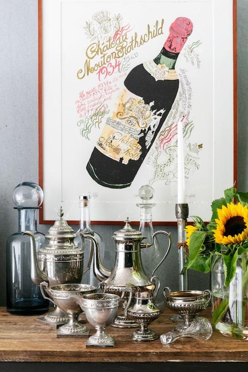 På ett avlastningsbord bredvid matbordet har Anette samlat nya och gamla kannor och pokaler i en grupp. Blå karaff, House Doctor. Ljusstake från Granit. Glaskarafferna är köpta på auktion liksom de två silverkannorna, pokalerna, gräddkannan och sockerskålen. Tavla av Catharina Göth.