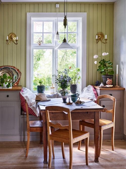 Det platsbyggda köket har en inbyggd sittbänk vid fönstret. Både väggar och skåp är målade i linoljefärg och trägolven såpas med jämna mellanrum.
