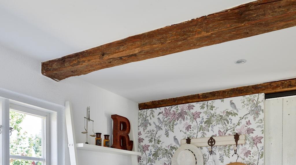I gästrummet har paret byggt en vägg och en skjutdörr av gammalt virke. Den gamla Grundig Radion och den fina skinnstolen hittade paret i huset när de köpte det.