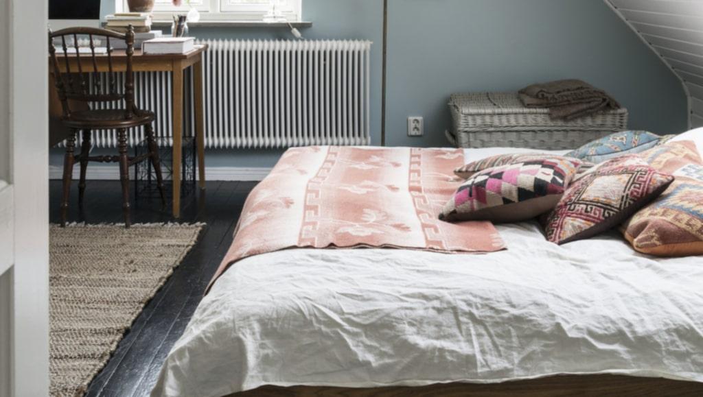 Sovrummet är målat i eb vacker blågrå ton. Kuddarna och filten är loppisfynd, skrivbordet är köpt på auktionsverk i Svedala. Tavlorna är köpta på loppis.