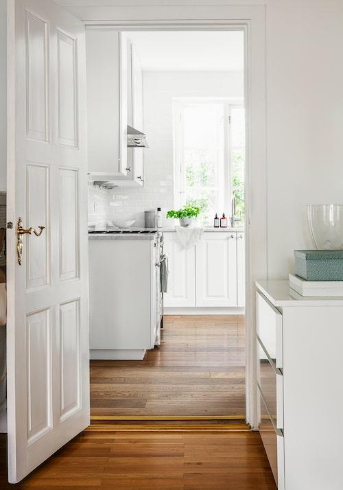 Vy mot köket från hallen. De mörka trägolven ska snart vitbetsas – Marielle vill ha vitt, vitt, vitt. Hallbyrå, Ikea.