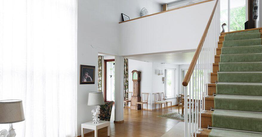 Intill entréhallen finns trappan upp till övervåningen, där man har utsikt ned mot sällskapsrummen.