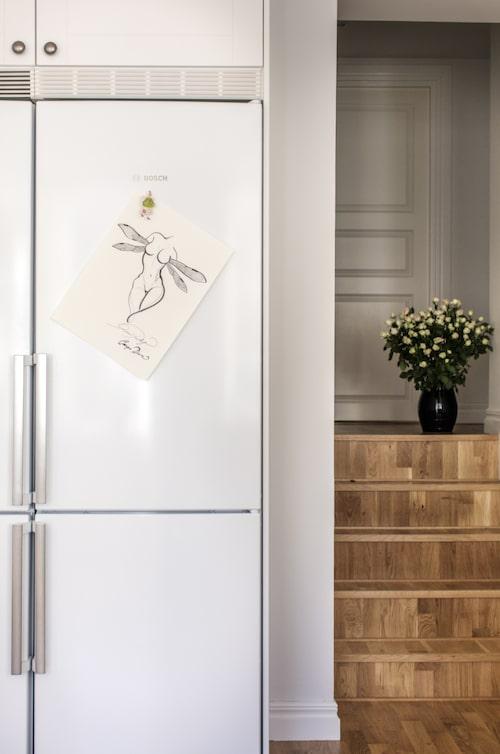 På kylskåpet hänger en ängel i svart tusch – en skiss till ett samarbete med Kosta Boda.