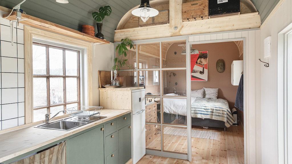 Kök och sovrum med glasfönster som avskärmar.