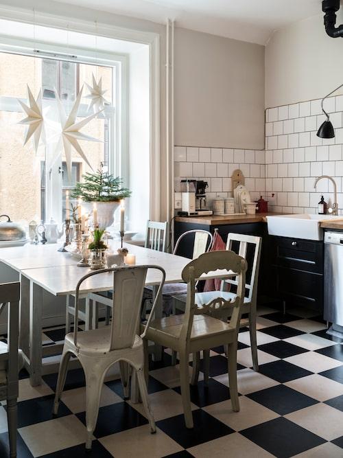 I köksfönstret hänger stjärnor i olika storlekar, några av de få saker i Amelies hem som är nyproducerade. Stolar i olika färger och former lyfter fram den personliga stilen i köket. Slagbord och stolar, loppis. Stjärnor, Rum21.