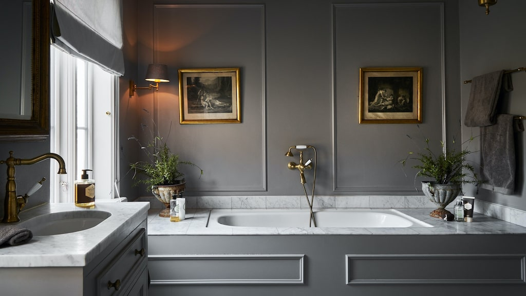 Påkostat badrum på nedre plan med inbyggt badkar, exklusiva mässingskranar i gammal stil och carraramarmor överallt.