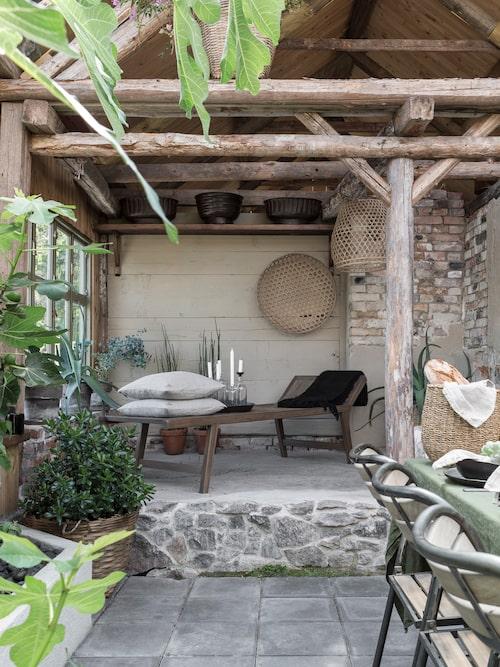 Den gamla murstocken har knackats ren från all gammal puts och ger orangeriet en rustik känsla. Dagbädd, auktionsfynd. Kuddar, Lovely Linen. Korgar på väggen Affarii, Glasflaskorna på dagbädden från Madam Stoltz, Hedegaards.
