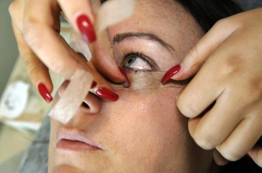Så här såg det ut när processen började. Behandlingen tar ungefär 2 timmar. Fransstylisten My Bäcklund förbereder genom att placera tejp under Melanies ögon.