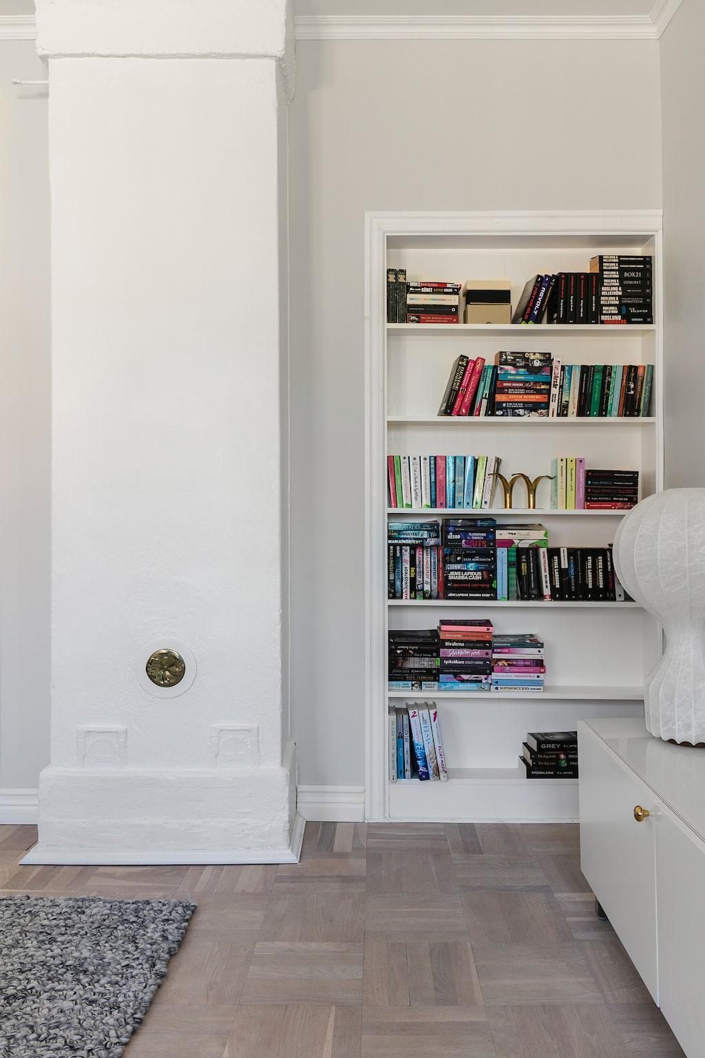 Den platsbyggda bokhyllan i vardagsrummet är Magnus verk. Här fanns tidigare en ingång till köket. Bordslampa från Flos.