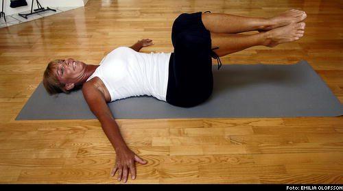 Liggande rotation 1. Ligg på golvet med benen i 90 grader. Placera armarna ut från kroppen med handflatorna i golvet för att stabilisera.