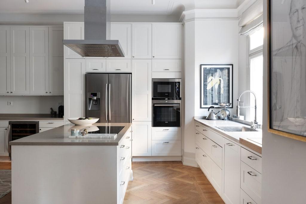 Här finns ett rymligt kök med skåp upp till taket, stor köksö med spishäll och matplats mitt i rummet.