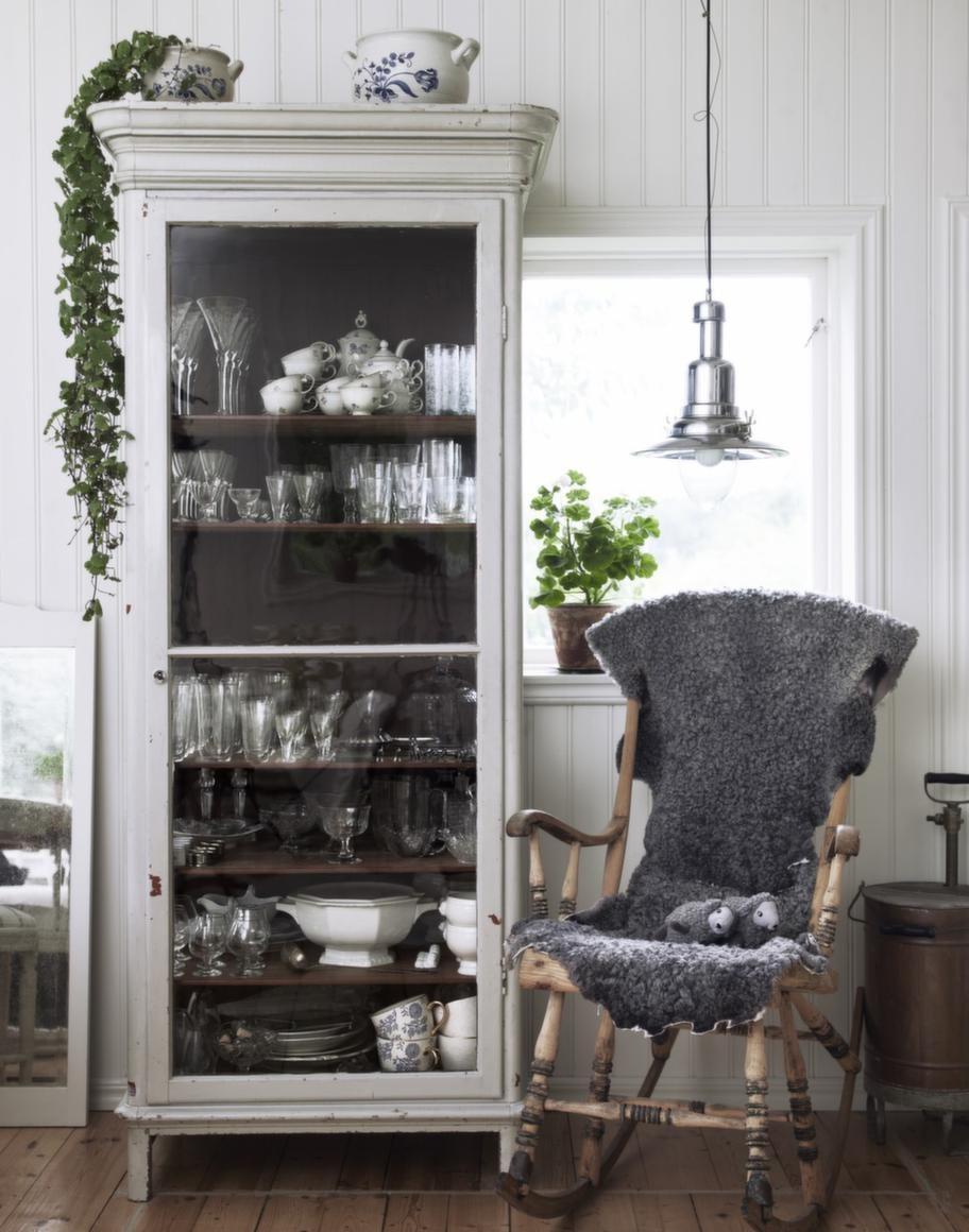 <strong>Gammalt skåp. </strong>Mellan köket och den gustavianska sittgruppen står det underbara gamla medicinskåpet, Marias första inköp av en antik möbel. Skåpet hittade hon i en antikaffär på Odengatan i Stockholm och har bland annat fyllt det med mormors gamla kaffeservis. Lampan är från Ikea, den fantastiska gungstolen är ett grovsopsfynd och pryds av grå fårskinnsfällar från Fårskinnsboden i Äppelviken.