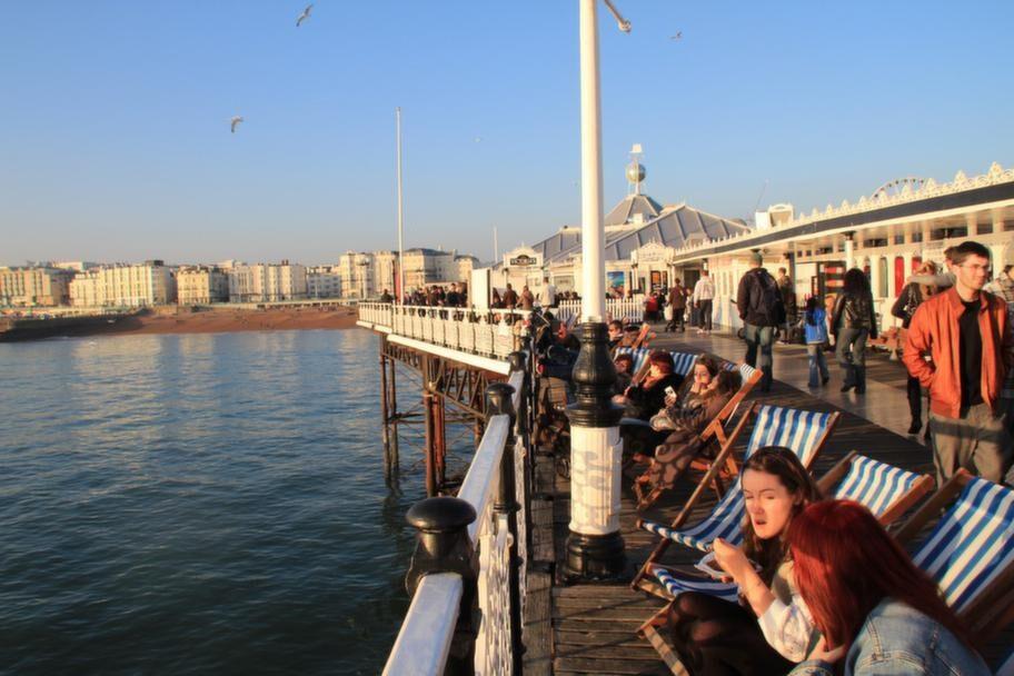 Brighton Pier i kvällssolen. Lista ut hur man fäller ut en klassisk randig solstol och njut.