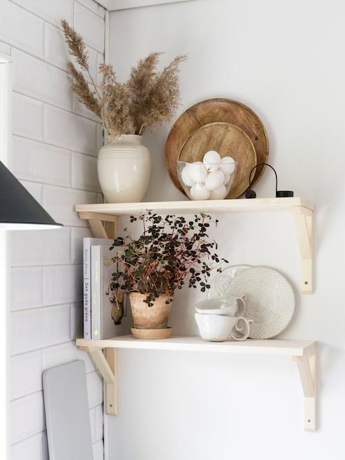 Med enkla konsoler och hyllplan i trä kan man lätt förändra sitt kök. På hyllan står bland annat Jennys egentillverkade keramik. Vas, Le Creuset. Kruka, Bergs Potter. Kakel, Höganäs.