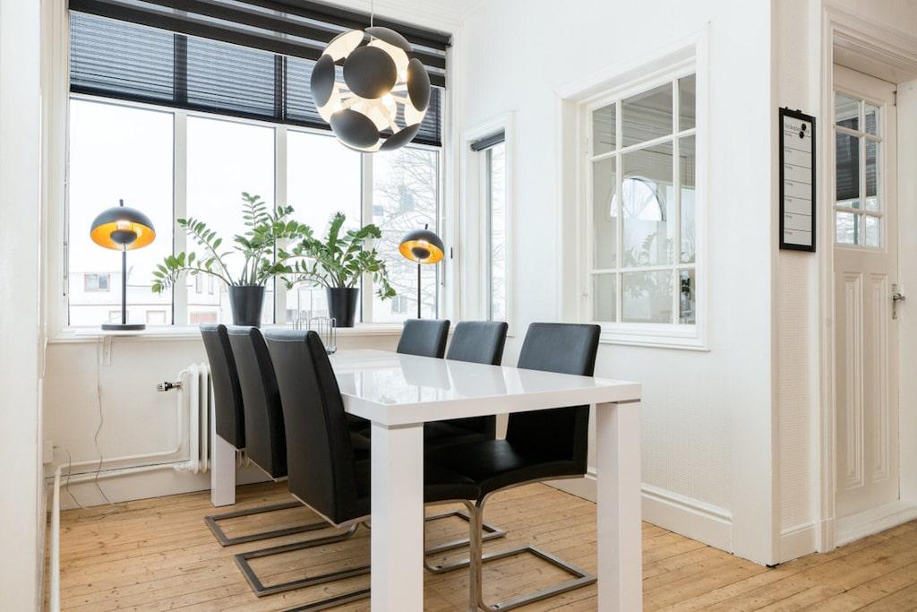 Rummet har en fin plats för matbordet i burspråket. För övrigt är det byggt i öppen lösning mot vardagsrummet. Väggarna är tapetserade med en vit akustiktapet som fortsätter in i vardagsrummet.