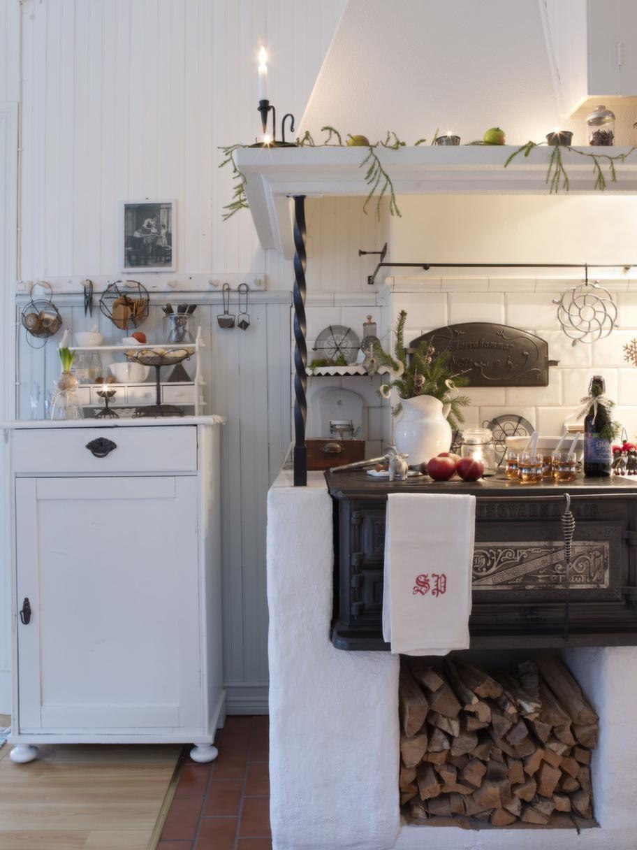 MYSIG SPIS<br>Vedspisen är kökets hjärta och värmer gott. Spiskupan skapar trevnad, den har Raimo byggt av spånskivor som han sedan har putsat.