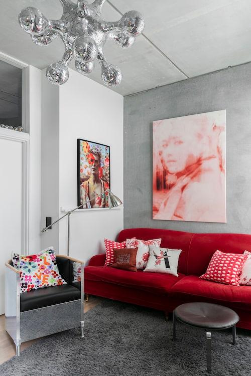 Den röda soffan som Anette och Pigge haft med sig från en tidigare bostad har fått ange tonen för inredningen. Aluminiumfåtöljen i svart skinn är designad av Mats Theselius, Källemo. Pall, PK33 av Poul Kjaerholm.  Discolampan i taket hittade Anette på Reform Furniture. Tavlan ovanför soffan har hon gjort själv. Kuddar från Svenskt Tenn och H&M Home.