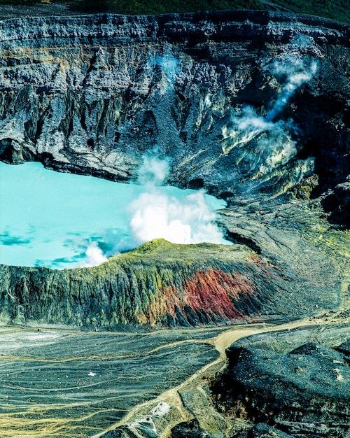 Vulkanen Poás krater är tre hundra meter djup och sjön i dess botten är mintgrön och ogenomskinlig. Ångorna dansar i slingor och slöjor över vattnet. Det är bara drygt femtio år sedan Poás senast hade ett utbrott.