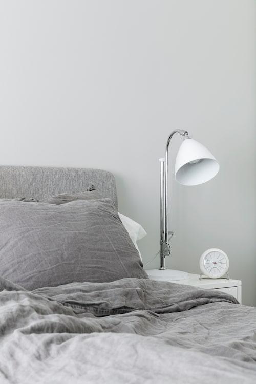 Färgerna är sobra i sängkammaren. Sängkläder från H&M Home. Sänglampa, från Bestlite. Väckarklocka från Arne Jacobsen.