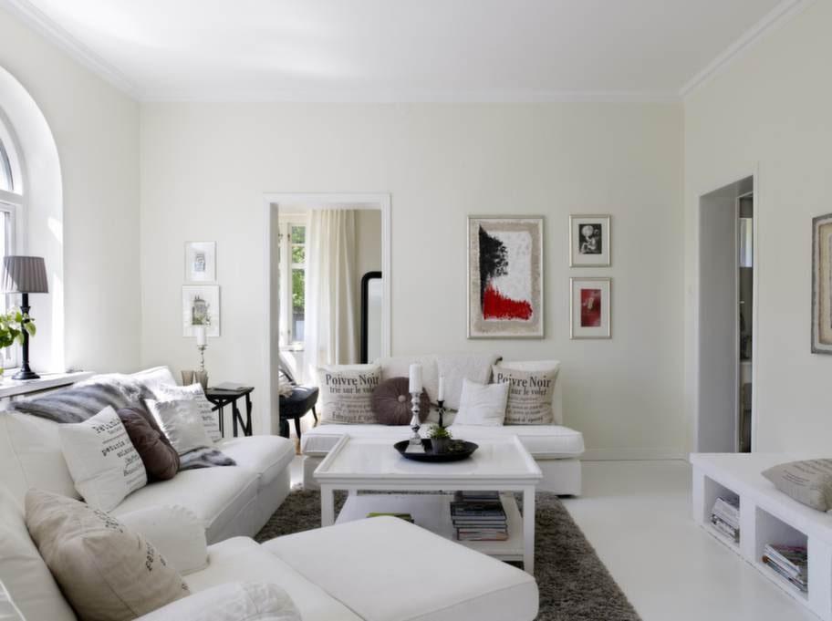 Annette och Fredrik tycker mycket om konst. Färgglada tavlor pryder väggarna och skapar liv i den ljusa inredningen. De stora färgglada tavlorna är målade av Annettes mamma. Vintavlorna av Håkansson. Rummet som skymtas bakom är det tidigare köket på 10 kvm.