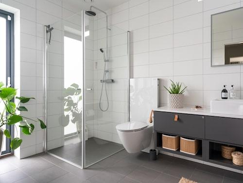 Badrummet är modernt inrett i grå och vita toner med inslag av brunt läder och förvaring i naturmaterial. Läderhandtag, Ballingslöv.