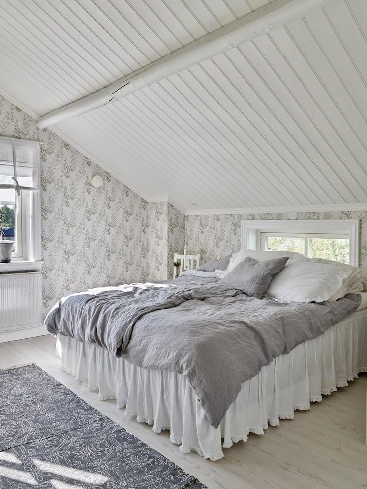 Elin och Tobias mysiga sovrum ligger under snedtaket på övre plan. Tapeten på väggen heter Scandinavia och kommer från Rusta. Sängkappa, Ellos.