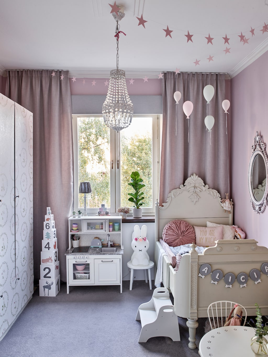 Alicias rum är en prinsessdröm i rosa. Hon har fått garderobsluckor i sin egen höjd i sitt rum. Linnea och Carsten köpte extra dörrar till garderoberna i Alicias rum och höjde upp de befintliga. Sedan sågade de till nya dörrar så att de blev som små luckor. På så vis behöver Alicia bara öppna de små dörrarna för att nå sina leksaker. Uppiffat lekkök, Ikea. Mörkläggande gardiner, Ohlssons tyger. Säng och spegel från Blocket. Glasballonger från Finebyme.nu. Garderober, Dombås, Ikea.  Garderoberna är tapetserade med tapeten Pyrola, Boråstapeter.