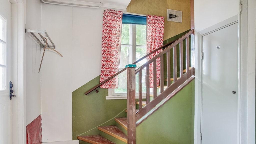 En trätrappa leder upp till övervåningen som ännu inte renoverats.