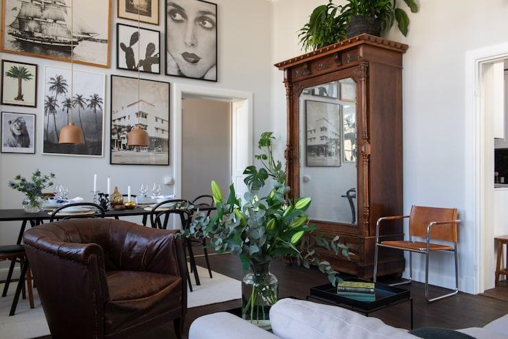 Vid matplatsen hänger en tavelvägg med motiv köpta på loppis blandat med fotoposters av Carolin Sallde och Carl Bengtsson.