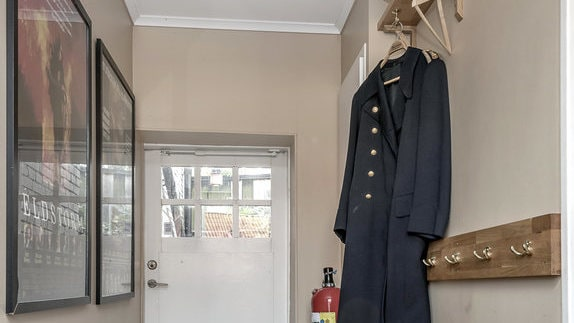 I hallen hänger en gammal brandmanskostym.