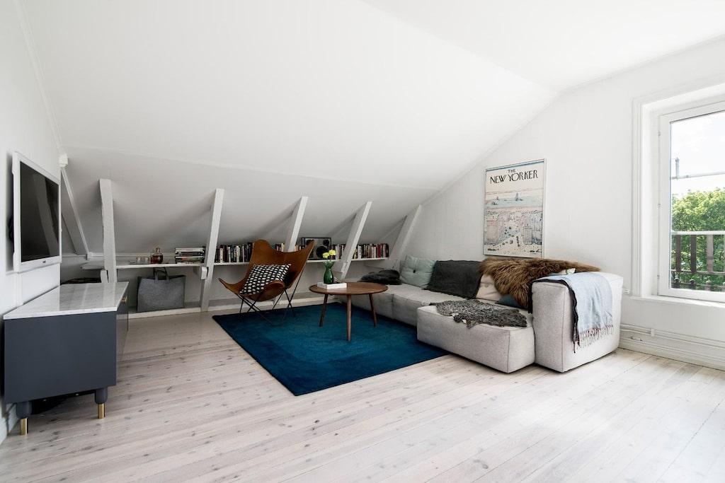 Charmigt vardagsrum med snedtak, synliga bjälkar och en vacker öppen spis. Man har öppnat upp kattvinden och skapat ytterligare yta, men framförallt en mysig koja för den lille. På motstående sida, en möblerbar nisch, perfekt som läshörna /bibliotek med arbetsplats. Plats för soffgrupp och tv-möbel.