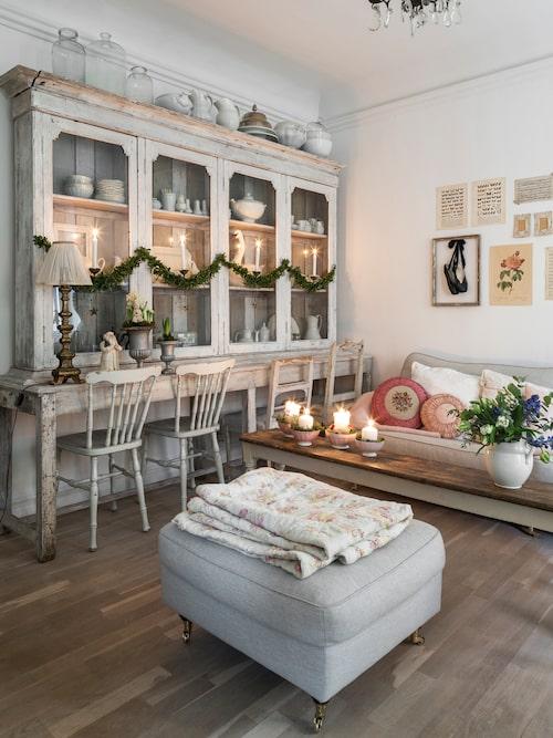 Längs ena väggen i vardagsrummet står Amelies favoritmöbel, ett stort vitrinskåp med vacker patina. Här försvaras det vita porslinet. Soffbord, Vintage by Nina. Soffa och pall, Trademax. Pläd, loppis. På väggen ett kollage av planscher, tagna ur gamla böcker och nothäften. Ett par svarta balettskor i en silverram bryter av mot den övriga inredningen. Soffbord, Vintage by Nina.