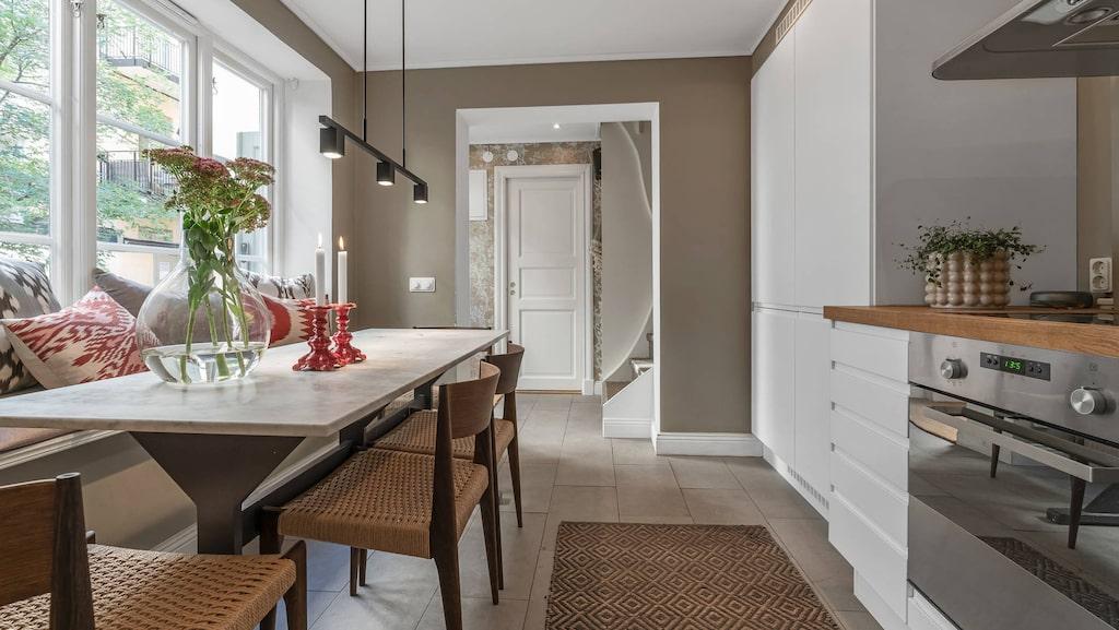 Vy från kök ut mot hall och trappa upp till andra våningen.