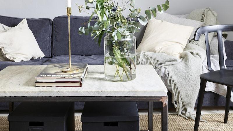 Vardagsrummet är inrett med en mix av grått, mässing och stål. Sisalmattan mjukar upp och binder ihop soffhörnan. Pläd, Cozy living, kuddar, Linum, skinnpuff, Wallboe interior, stol, Ikea, golvlampan är second hand, soffa, Mio.
