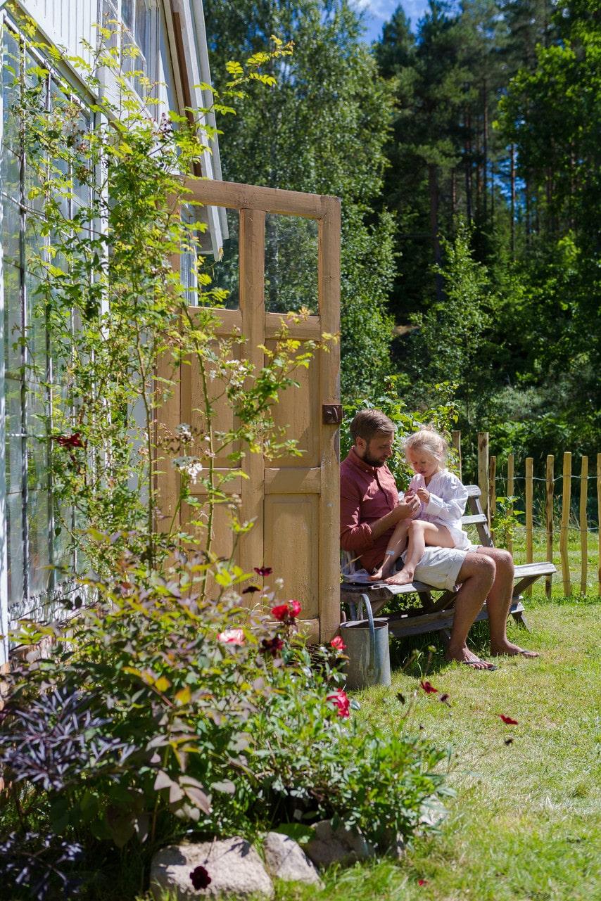 Johan och dottern Viola utanför det vackra växthuset.