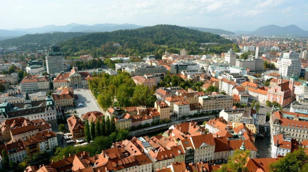 Från slottskullens topp har du utsikt över den gulliga staden, med de röda taken och de närliggande alptopparna.