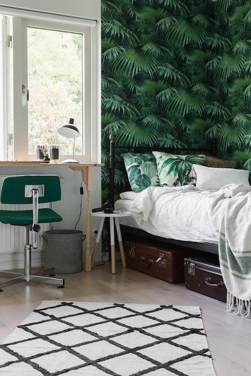 Inne hos Vira växer grönskan från golv till tak. Färgen plockas upp även på sängkläder och skrivbordsstol. Här syns ett egensnickrat träbord med snyggt svarvade ben. Under sängen finns plats för praktisk förvaring i form av charmiga gamla resväskor. Tapet från Midbec.