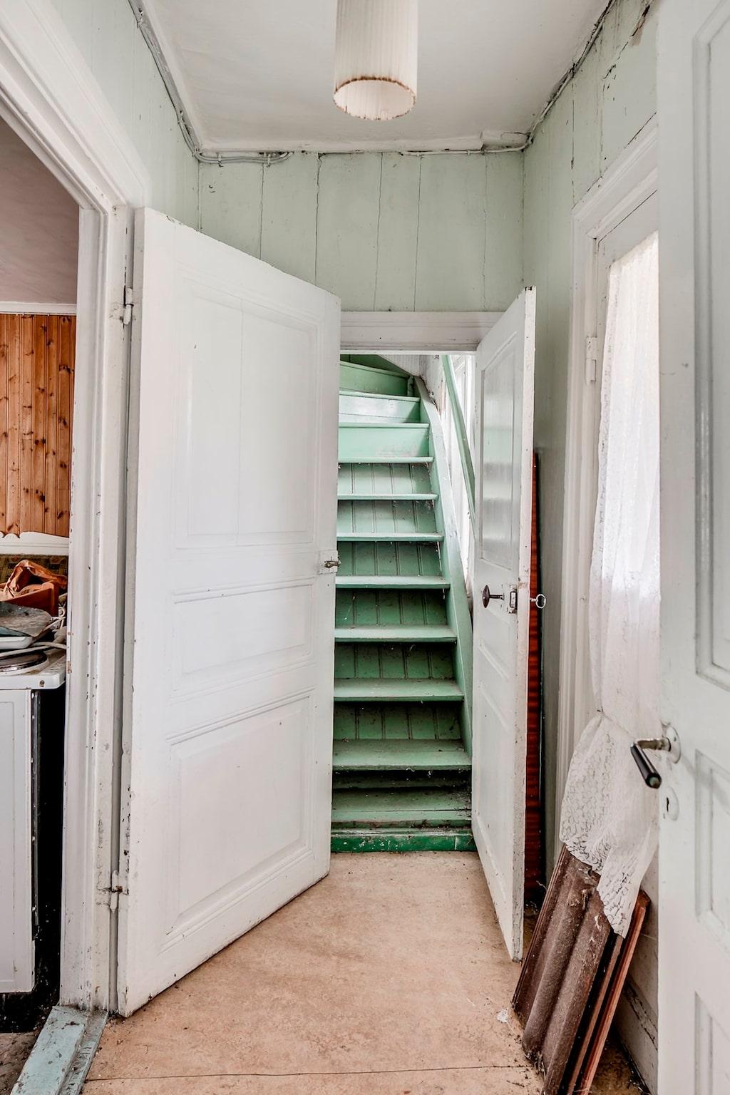 En grön trätrappa leder upp till andra våningen.
