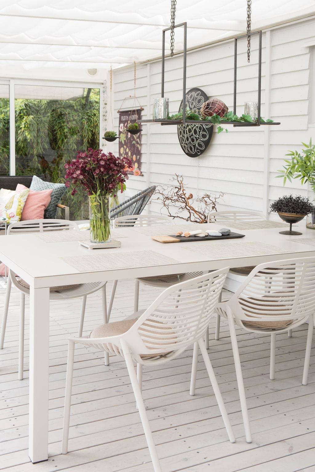 Matplatsen domineras av ett generöst bord och stolar från Hulténs i Staffanstorp. Lampan ovanför bordet är från Majas Cottage, Lorensdal. Den runda väggbelysningen kommer från Ting Ute & Inne.