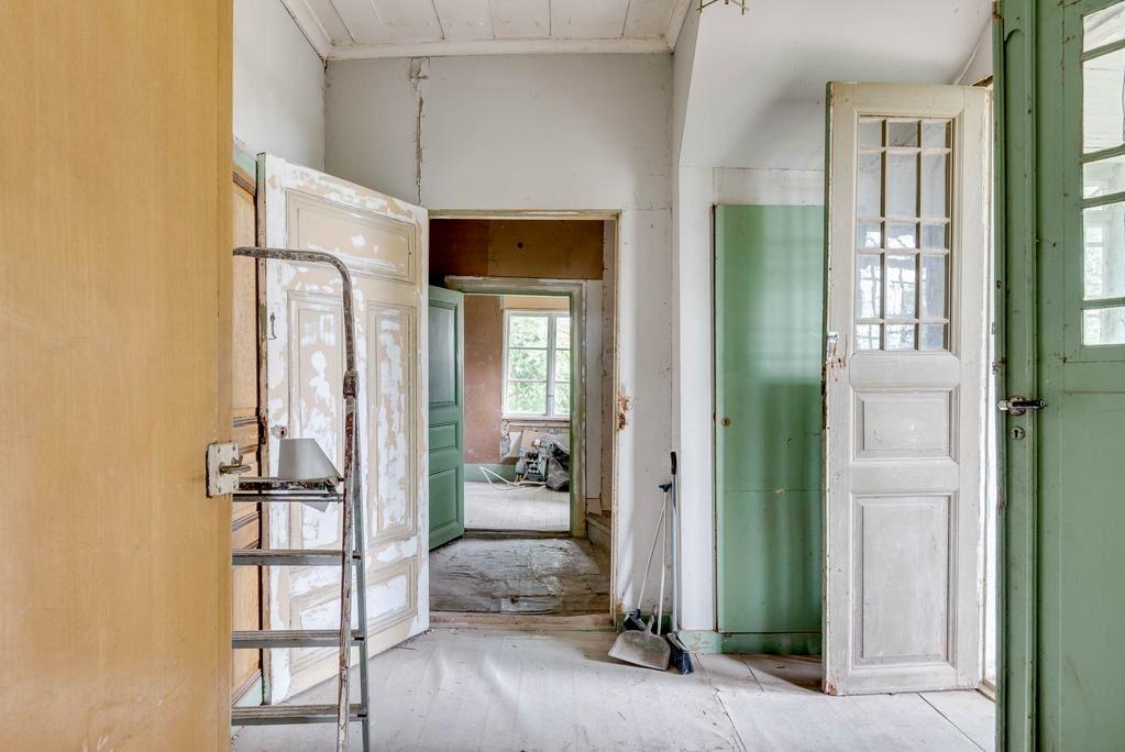 Hall med trägolv och tapetserade väggar.